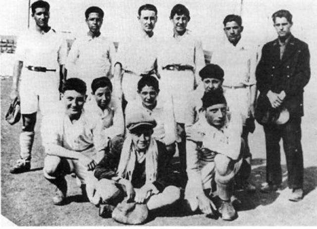 Camus au premier plan avec le foulard avec son équipe de foot (soccer) avant que la tuberculose ne l'empêche de jouer comme gardien de but.