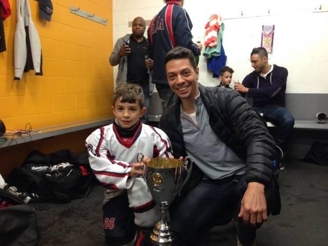 Rohan tenant la coupe, avec son papa qui participe à l'entraînement de l'équipe.