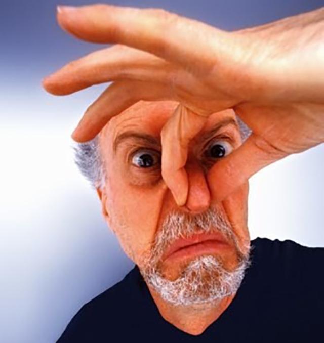 Mature man holding nose, portrait