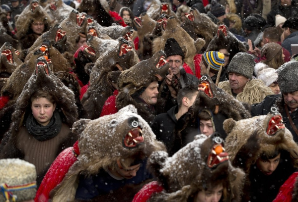 People wearing bear furs perform during a festival of New Year ritual dances attended by hundreds in Comanesti, northern Romania, Wednesday, Dec. 30 2015. In pre-Christian rural traditions, dancers wearing colored costumes or animal furs, toured from house to house in villages singing and dancing to ward off evil, in the present the tradition has moved to Romania's cities too, where dancers travel to perform the ritual for money.(AP Photo/Vadim Ghirda)